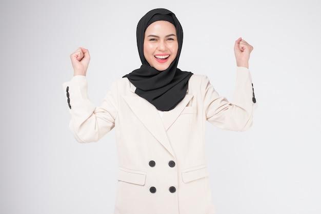 흰색 배경 스튜디오 위에 히잡으로 양복을 입고 웃는 젊은 이슬람 사업가의 초상화.