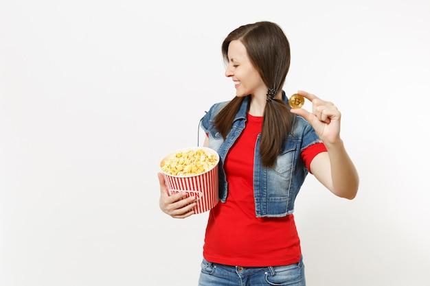 흰색 배경에 격리된 팝콘과 비트코인 양동이를 들고 영화 영화를 보고 있는 캐주얼한 옷을 입고 눈을 감고 웃고 있는 젊고 예쁜 브루네트 여성의 초상화. 영화 개념의 감정.