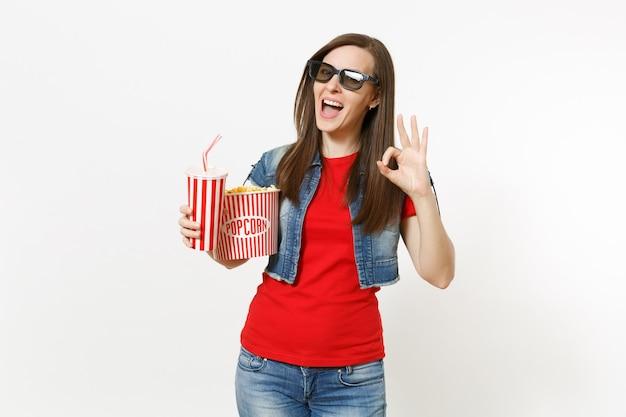 3d 안경을 쓰고 팝콘 양동이와 소다 또는 콜라 플라스틱 컵을 들고 흰색 배경에 격리된 괜찮은 표시를 보여주는 3d 안경을 쓰고 웃고 있는 젊은 예쁜 여성의 초상화. 영화 속 감정.