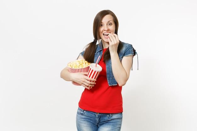 캐주얼한 옷을 입고 영화 영화를 보고, 양동이에서 팝콘을 먹고, 흰색 배경에 격리된 플라스틱 컵의 소다 또는 콜라를 들고 웃고 있는 젊고 예쁜 여성의 초상화. 영화 개념의 감정.