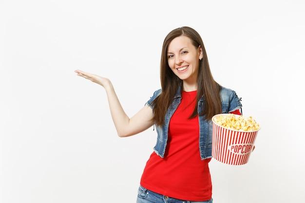 흰색 배경에 격리된 복사 공간을 옆으로 가리키며 팝콘 양동이를 들고 영화 영화를 보고 있는 캐주얼한 옷을 입고 웃고 있는 젊고 예쁜 여성의 초상화. 영화 개념의 감정.