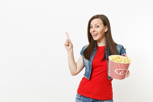 캐주얼한 옷을 입고 영화를 보고 웃고 있는 젊은 여성의 초상화, 팝콘 양동이를 들고 흰색 배경에 격리된 복사 공간을 검지 손가락으로 가리키고 있습니다. 영화 개념의 감정