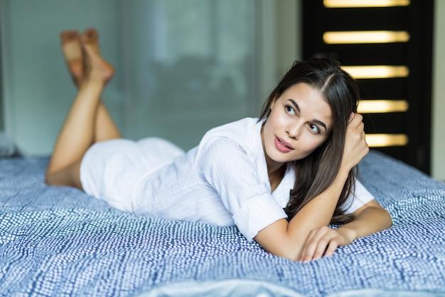 Портрет молодой усмехаясь милой женщины лежит в кровати внутри помещения.
