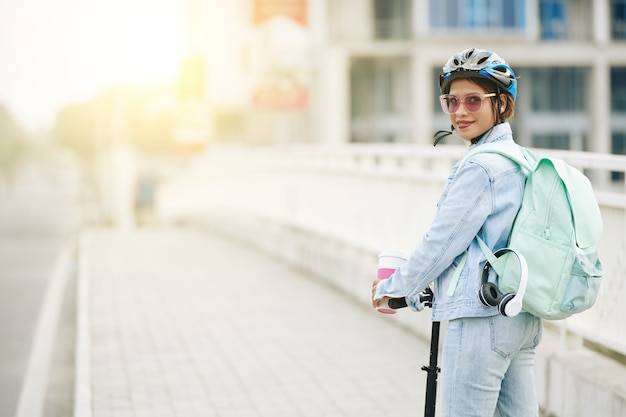 큰 배낭을 메고 전기 스쿠터를 탈 때 보호용 헬멧을 쓰고 웃고 있는 젊고 예쁜 여성의 초상화