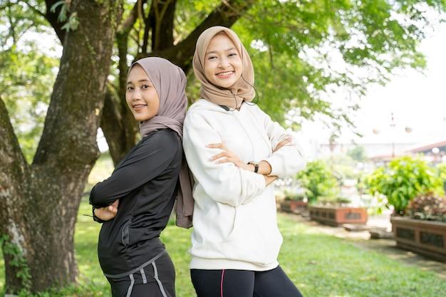 Портрет молодой улыбающейся спортивной мусульманской женщины, стоящей друг против друга, глядя в камеру на открытом воздухе