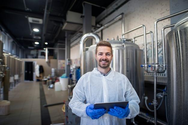 Портрет молодого улыбающегося технолога с таблеткой на производственном предприятии.