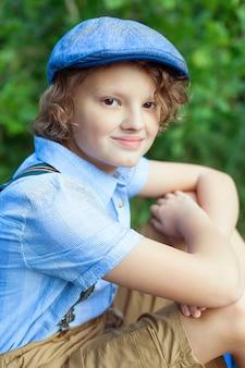 Портрет молодого усмехаясь предназначенного для подростков мальчика. гулять по парку