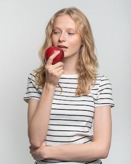 Портрет молодой улыбающейся женщины, кусающей красное яблоко. свежее лицо, естественная красота