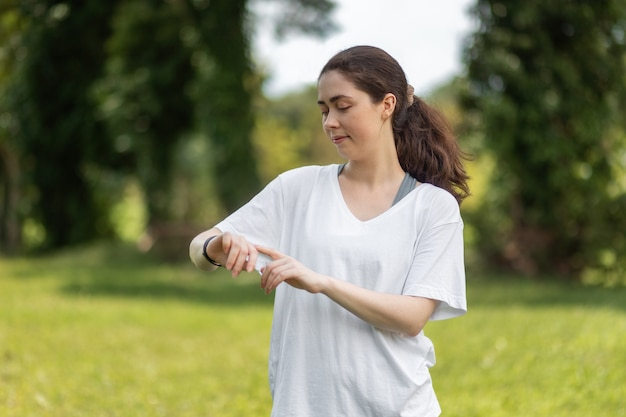 Портрет молодой улыбающейся женщины проверяет ее умные часы. концепция современного устройства и велнеса
