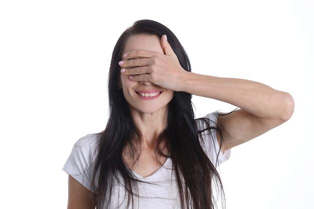손 클로즈업으로 그녀의 눈을 덮고 웃는 젊은 여자의 초상화