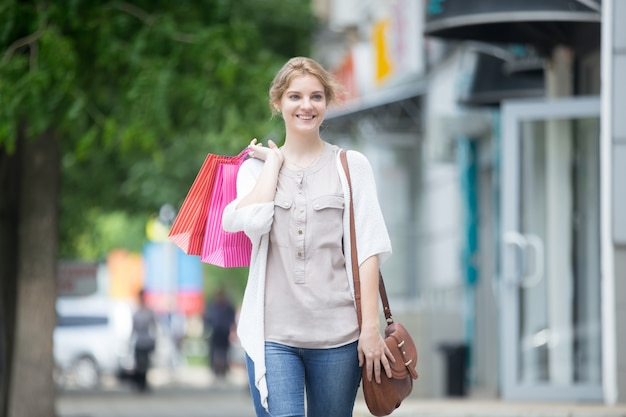 쇼핑 시간을 즐기는 젊은 웃는 여자의 초상화