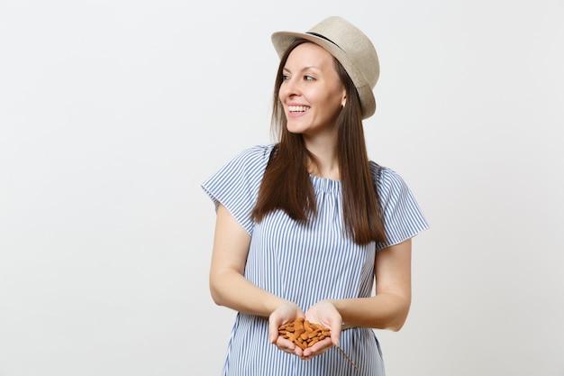 Портрет молодой улыбающейся женщины, держащей в руках коричневые необработанные орехи миндаля, изолированные на белом фоне. правильное питание, веганское питание, вегетарианское питание, концепция диеты здорового образа жизни. копировать пространство