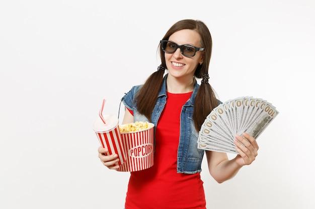 3d 안경을 쓰고 팝콘 양동이, 탄산음료 또는 콜라 한 컵, 달러 묶음, 흰색 배경에 격리된 현금을 들고 영화를 보고 있는 웃고 있는 젊은 여성의 초상화. 영화 속 감정.
