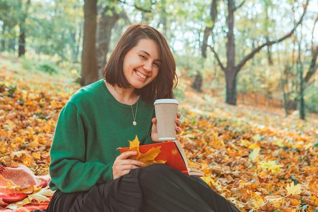 Портрет молодой улыбающейся женщины в осеннем желтом парке. падающие листья