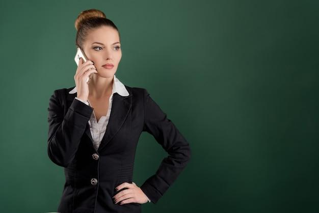 Портрет молодой улыбающейся женщины в деловой одежде, разговаривает по телефону