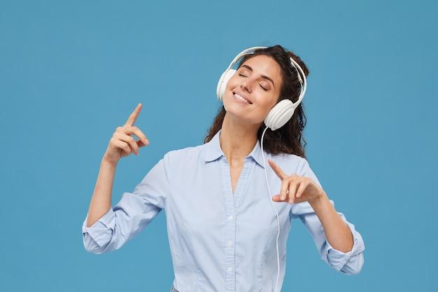 Портрет молодой улыбающейся женщины в наушниках, слушающей музыку и наслаждающейся ею на синем фоне