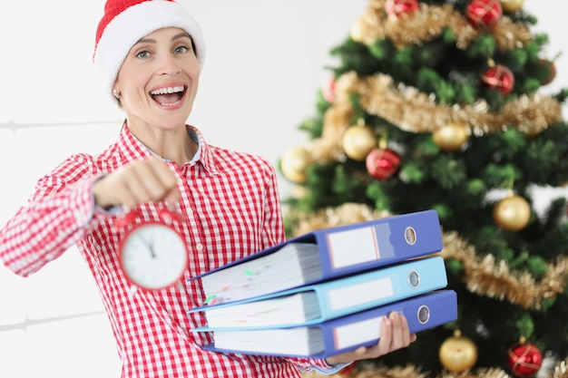 Портрет молодой улыбающейся женщины в шляпе санта-клауса держит будильник и деловые документы на