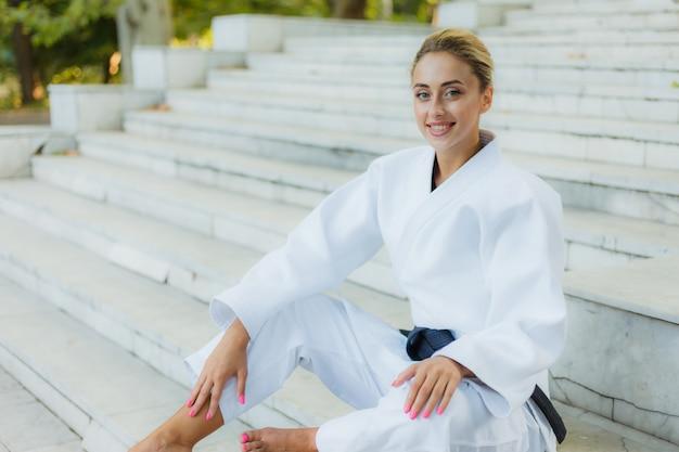 Портрет молодой усмехаясь женщины в белом кимоно с черным поясом. спортивная женщина сидит на лестнице на открытом воздухе. боевые искусства