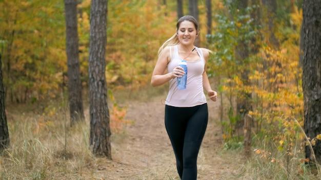 Портрет молодой улыбающейся женщины, бегающей трусцой и держащей бутылку воды.