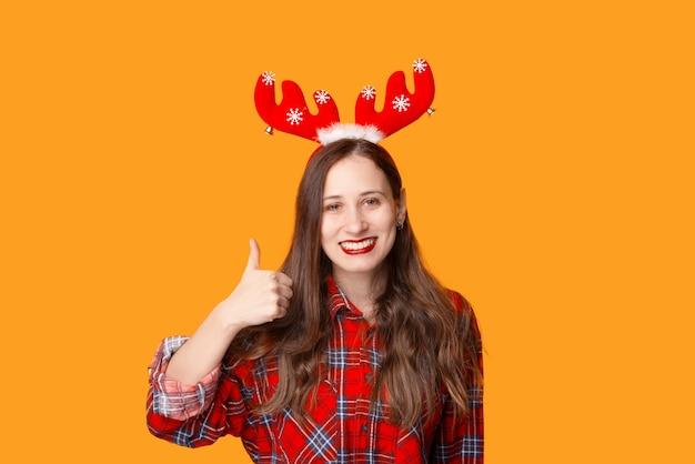 Портрет молодой улыбающейся женщины, готовой к празднику рождества и показывая большой палец вверх