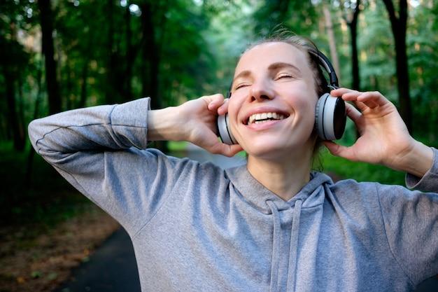 Портрет молодой улыбается женщина отдыхает после пробежки и слушать музыку. здоровый спортивный образ жизни. фитнес и тренировки на открытом воздухе.