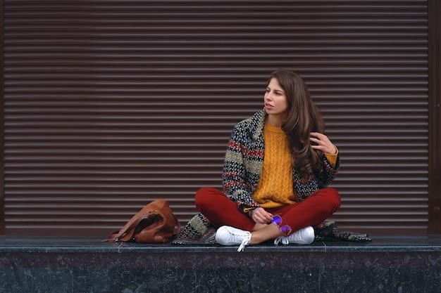 ヨーロッパの都市の通りでポーズをとって、足を組んで座っている若い笑顔の女性の肖像画。