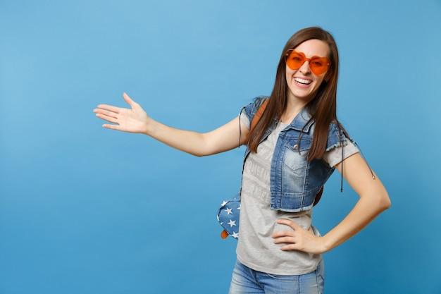 青い背景で隔離の手を脇に向けてオレンジ色のハートのメガネを身に着けているバックパックとデニムの服を着た若い笑顔の女性学生の肖像画。大学での教育。広告用のスペースをコピーします。