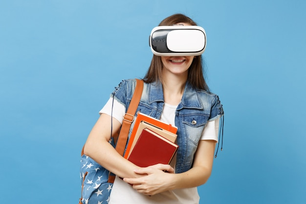 Портрет молодой улыбающейся студентки в джинсовой одежде с рюкзаком в очках виртуальной реальности, держа школьные учебники, изолированные на синем фоне. обучение в средней школе университетского колледжа.