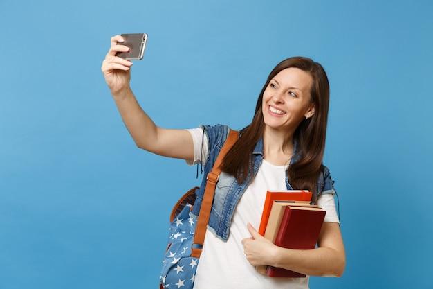 Портрет молодой улыбающейся женщины-студента с рюкзаком, держащим школьные учебники, делая селфи-съемку на мобильном телефоне, изолированном на синем фоне. образование в концепции колледжа университета средней школы.