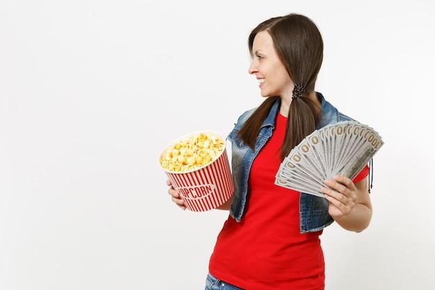 영화 영화를 보고 웃고 있는 젊은 여성의 초상화, 팝콘 양동이와 달러 묶음, 현금 돈, 흰색 배경에 격리된 복사 공간을 제쳐두고 바라보고 있습니다. 영화 개념의 감정.
