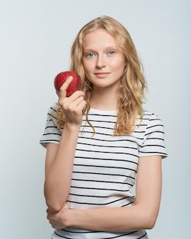 Портрет молодой улыбающейся женщины с красным яблоком свежее лицо естественной красоты