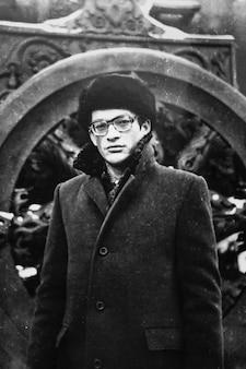 겨울에는 코트와 모자를 쓴 안경을 쓴 젊은 소련 남자의 초상화. 1980년대 빈티지 흑백 종이 사진. 양도된 재산, 가족 기록 보관소. 오래된 품질, 소프트 포커스