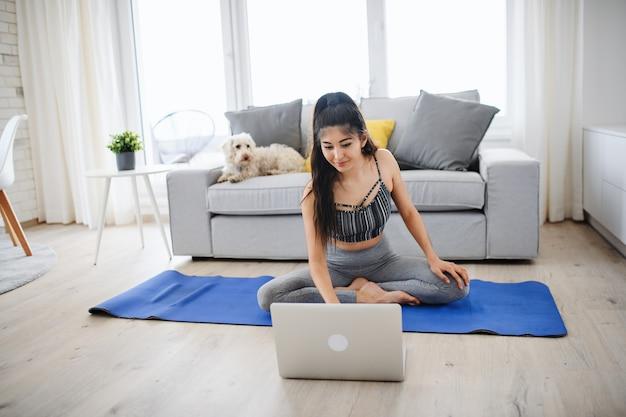 집에서 실내에서 운동을 하는 노트북을 가진 젊은 스포츠 여성의 초상화, 건강한 생활 방식 개념.