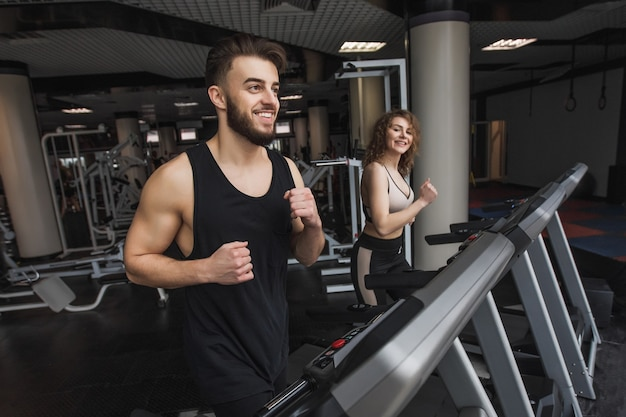 現代のジムで有酸素運動をしている若いスポーツカップルの肖像画