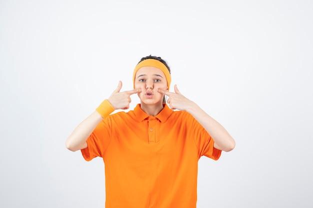 그녀의 뺨을 꼬 집는 주황색 옷에 젊은 sportswoman의 초상화.