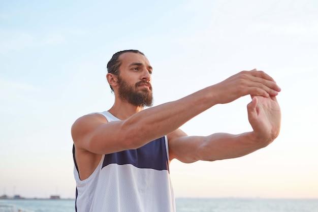 海辺で朝のヨガをしている若いスポーティなひげを生やした男の肖像画は、健康的なアクティブなライフスタイルを導き、目をそらします。フィットネス男性モデル。