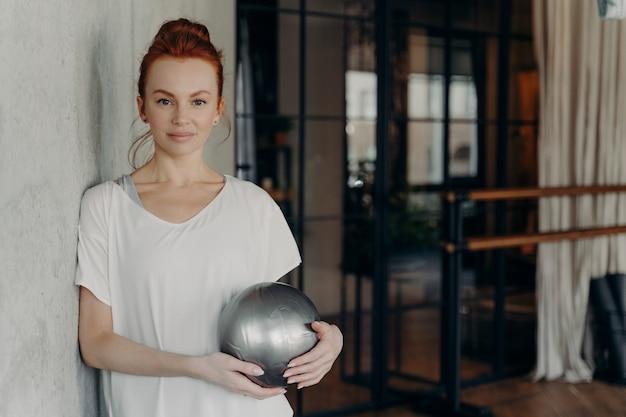 필라테스 수업 후 손에 미니 핏볼을 들고 있는 스포티하고 건강한 생강 여성의 초상화, 피트니스 스튜디오에서 벽에 기대어 운동 사이에 휴식, 체육관에서 휴식 시간 즐기기