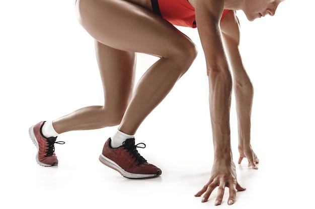흰색 스튜디오 배경 위에 격리된 경주 시작 블록에서 스포티한 젊은 여성의 초상화. 단거리 선수, 조깅하는 사람, 운동, 운동, 피트니스, 훈련, 조깅 개념. 프로필