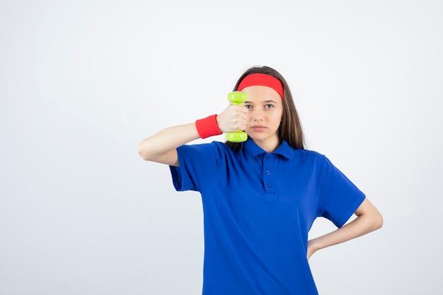 아령을 들고 파란색 티셔츠에 젊은 스포티 한 여자의 초상화. muñequera roja
