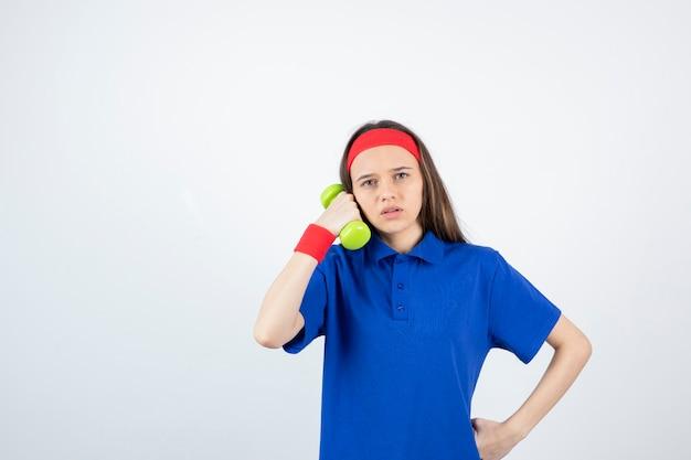 아령과 파란색 티셔츠 훈련에 젊은 스포티 한 여자의 초상화.
