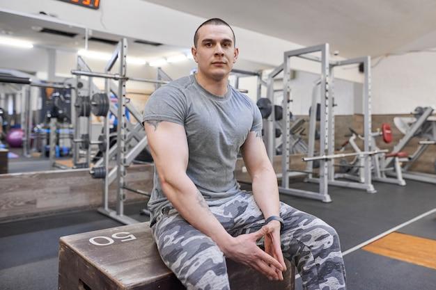 체육관에서 젊은 강한 웃는 근육질 웃는 남자의 초상화.