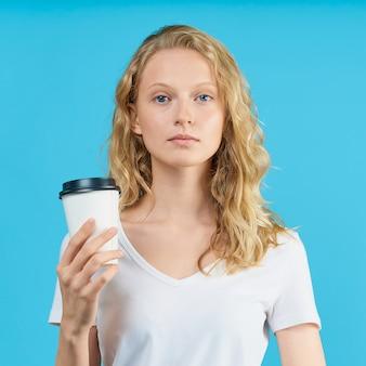 Портрет девушки молодого студента с чашкой кофе на стене ярко-синего цвета.