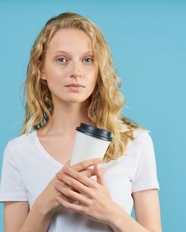 Портрет молодой девушки студента с чашкой кофе на стене нейтрального тона цвета голубой.