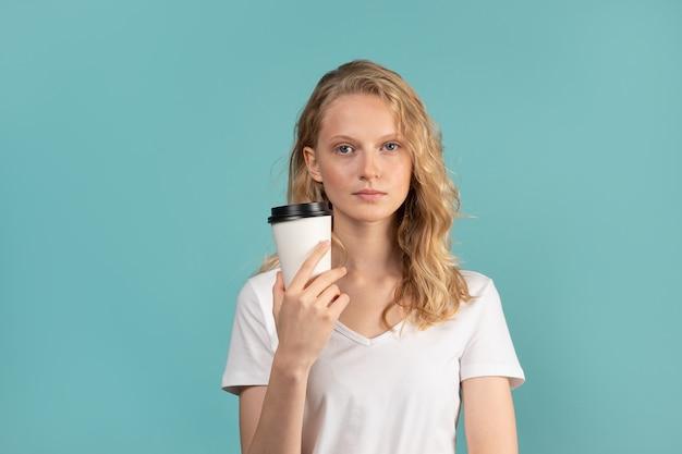 Портрет молодой студентки с чашкой кофе на зеленой стене