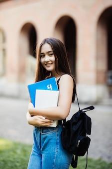 Портрет молодой студент, держа книгу в кампусе на открытом воздухе