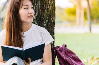 Portrait of young student or asian student happily reading a book on the lawn