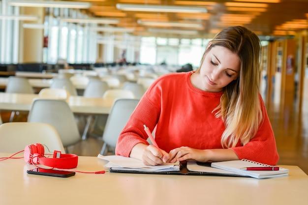 大学図書館で勉強している若い学生の肖像画。教育とライフスタイルの概念。