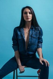 Портрет молодой стильной моды гламурной сексуальной женщины брюнет джинсовая одежда.