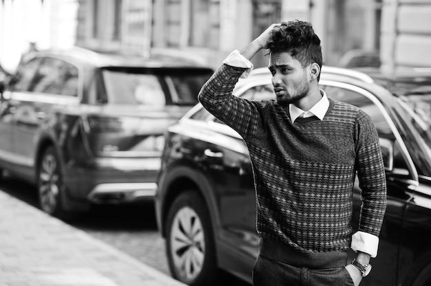 若いスタイリッシュなインド人モデルの肖像画は、suv車に対して通りでポーズします。