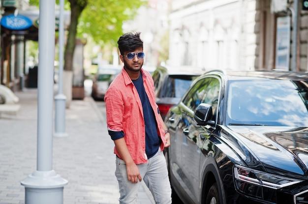 車に対してサングラスをかけて通りでポーズをとる若いスタイリッシュなインド人モデルの肖像画。